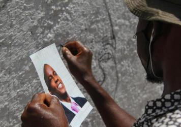 An artist who goes by the name Jamesy Jay paints a mural of slain Haitian president Jovenel Moïse on the road leading to the president's private residence above Port-au-Prince.