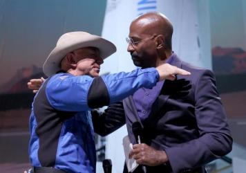 Jeff Bezos hugs Van Jones, founder of Dream Corps, on Tuesday after announcing a $200 million award to him and chef José Andrés for charities of their choice.