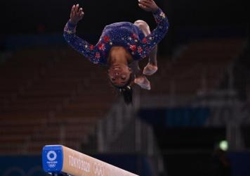 Simone Biles competes in the artistic gymnastics balance beam event of the women's qualification during the Tokyo 2020 Olympic Games at the Ariake Gymnastics Centre in Tokyo. The U.S. will face off with other top qualifiers early Tuesday.