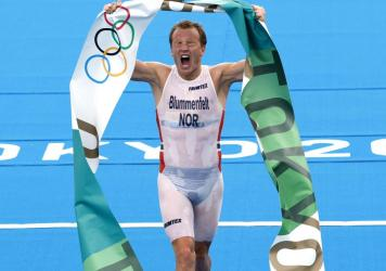 Norway's Kristian Blummenfelt celebrates as he crosses the line Monday to win the men's triathlon at the Tokyo Olympics. Blummenfelt won after a miscommunication between a media boat and the starting officials caused a rare false start in the endurance r