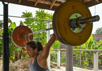 Hidilyn Diaz of the Philippines lifts weights during a training session on May 21 in the Malaysian city of Malacca. She had been stuck in Malaysia because of the pandemic.