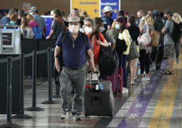Travelers head to a security checkpoint at Denver International Airport on July 2. The economy likely surged in the April-June quarter as vaccine rollouts sparked a surge in pent-up activity. A slowdown is now seen as inevitable, although the pace of gro