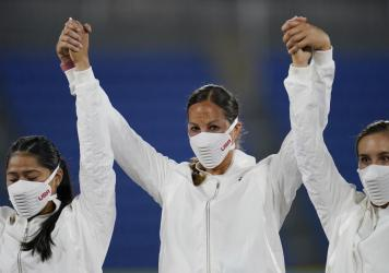 Members of the U.S. women's softball team raise their arms and wear special masks at the medal ceremony at the Summer Olympics in Yokohama, Japan.