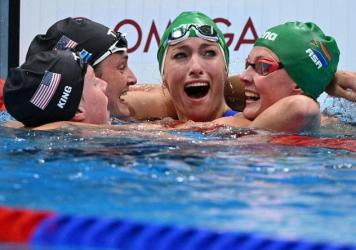 South Africa's Tatjana Schoenmaker, second from right, cheers with teammate Kaylene Corbett, right, and medalists Annie Lazor and Lilly King of Team USA after winning the final of the women's 200m breaststroke swimming event at the Tokyo Aquatics Centre