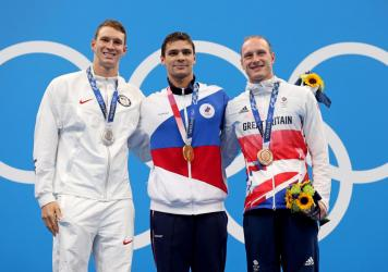 Silver medalist Ryan Murphy of Team USA (from left), gold medalist Evgeny Rylov of the Russian Olympic Committee and bronze medalist Luke Greenbank of Great Britain during Friday's medal ceremony for the men's 200-meter backstroke final at the Tokyo Game