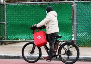 A DoorDash delivery person rides their bike in New York City. Workers across the country went on strike on July 31 to demand higher pay and tip transparency.
