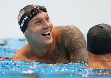 U.S. star Caeleb Dressel reacts after winning the gold medal and breaking the Olympic record in the men's 50 meter freestyle final at the Tokyo Olympics.