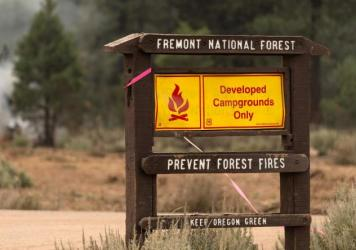 A fire warning sign is seen amid trees which smolder and burn in Division Echo Echo of the Bootleg Fire on July 25, 2021, in the Fremont National Forest of Oregon.