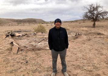 Carlos Yazzie's brother, Chris, stands next to the remains of their childhood home on the Navajo Nation.
