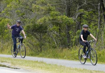 President Biden rides his bike in Rehoboth Beach, Del., earlier this year with first lady Jill Biden. The family has a beach house nearby.
