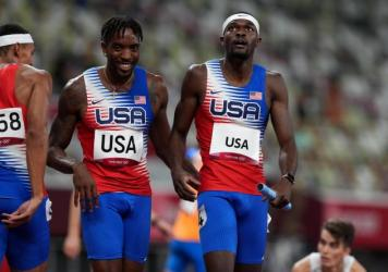 USA's Michael Cherry (left) and Rai Benjamin after winning gold in the men's 4 x 400 meter relay at the Olympic Stadium in Japan on Saturday.