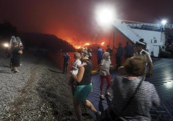 People evacuate from a wildfire north of Athens, Greece, on Friday. A climate-driven heat wave helped create conditions for the fire to burn out of control. Scientists warn that humans are running out of time to curb greenhouse gas emissions and avoid ca