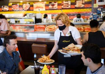 A server delivers food to customers dining at a restaurant in Los Angeles on Aug. 7. Restaurants are boosting pay to attract workers, and that could have an impact on already-high inflation.
