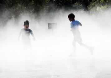 Children cool off in a misting pool at a park in Queens, N.Y., as temperatures reach into the 90s and with a heat index of over 100 degrees on Thursday.