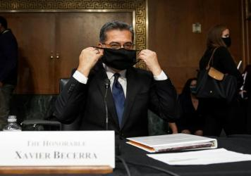 Xavier Becerra, then nominee for secretary of Health and Human Services, puts on his protective mask at his Senate Finance Committee confirmation hearing in February.