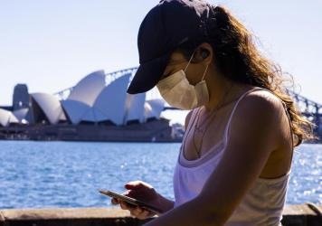 A woman looks at her phone outside the The Royal Botanic Gardens in Sydney, Australia on Aug. 6. The Indicator from Planet Money spoke to an economist for advice on how to cut back on digital dependency.