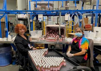 Alice Gomez and Maria Ramos work at Dr. Bronner's soap factory in Vista, Calif. The company is doing weekly coronavirus testing but still wants all its workers vaccinated.