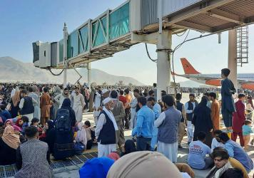 Afghans crowd the tarmac of the Kabul airport on Monday to flee the country. Thousands of people mobbed the city's airport trying to flee the group's feared hardline brand of Islamist rule.