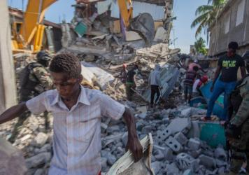 Haitians in Les Cayes assess the damage Sunday after a magnitude 7.2 earthquake struck a day earlier.