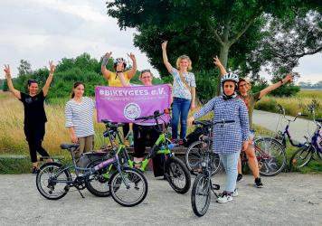 Volunteers and trainees with the group Bikeygees at a park in Berlin in July. The organization teaches refugee women in Germany how to ride bikes. Trainee Shapol Bakir-Rasoul, a refugee from Iraq, holds up a Bikeygees sign with founder Annette Krüger, r