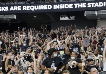 Raiders fans do the wave during last weekend's preseason game in Las Vegas as a stadium sign reminds them to wear face masks. The team now says spectators will have to show proof of vaccination — and that no masks will be required for those who have be