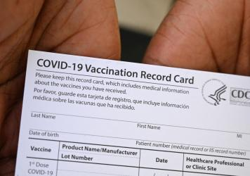 A health care worker displays a COVID-19 vaccination record card at a health center in Los Angeles earlier this month.