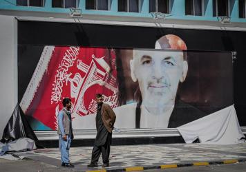 Men stand next to a torn poster of ousted Afghan President Ashraf Ghani at the Kabul airport on Monday. Ghani fled Afghanistan over the weekend as Taliban forces closed in on Kabul.