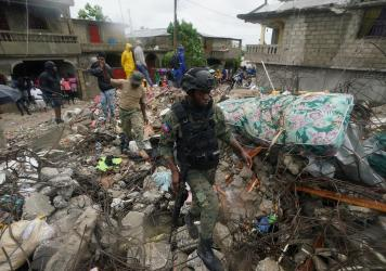 A soldier walks over earthquake rubble on Tuesday, the morning after Tropical Storm Grace swept over Les Cayes, Haiti, three days after the 7.2 magnitude quake.