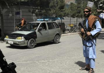 """Taliban fighters stand guard at a checkpoint in the city of Kabul, Afghanistan, Wednesday, Aug. 18, 2021. The Taliban declared an """"amnesty"""" across Afghanistan Tuesday seeking to convince a wary population that they have changed."""