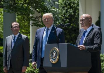 Then-Health and Human Services Secretary Alex Azar (left) and President Donald Trump listen as Moncef Slaoui of Operation Warp Speed speaks about the crash program to develop a COVID-19 vaccine in the White House Rose Garden in May 2020.