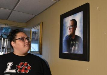 Stephanie Rimel looks at a photo of her brother Kyle Dixon, 27, who died of COVID-19 on Jan. 20. She says that during his illness and after his death, some people made insensitive comments or denied the pandemic's reality.