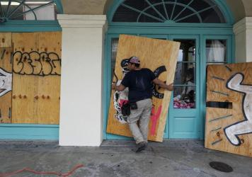 In preparation of Hurricane Ida, a workers attach protective plywood to windows and doors of a business in the French Quarter in New Orleans on Saturday.