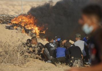 Protesters take cover next to tires on fire near the fence of Gaza Strip border with Israel during a protest east of Khan Younis, southern Gaza Strip, on Wednesday.