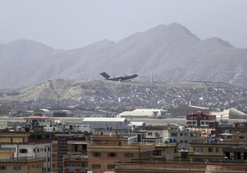 """A U.S. military aircraft takes off at the Hamid Karzai International Airport in Kabul, Afghanistan, Saturday. President Biden warned another attack at the airport is """"highly likely."""""""