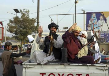 Taliban fighters wave from the back of a pickup truck, in Kabul, Afghanistan, Monday, Aug. 30, 2021. Many Afghans are anxious about the Taliban rule and are figuring out ways to get out of Afghanistan.