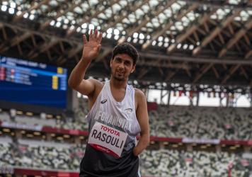 Hossain Rasouli of Team Afghanistan waves after competing in the Men's Long Jump-T47 Final at the Tokyo Olympic Stadium on Tuesday. He and teammate Zakia Khudadadi managed to get to Tokyo despite the turmoil in their home country.