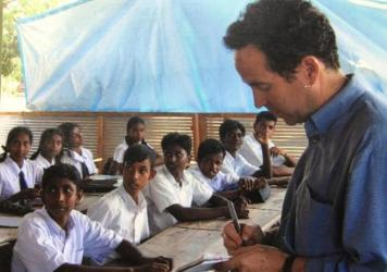 """Joel Charny, who's been a humanitarian aid worker for 40 years, talks to students at a camp for internally displaced people in northern Sri Lanka in 2005. It's one of his favorite photos, he says, """"because this is what I did hundreds of times: interview"""