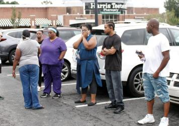 Anxious parents stand in the parking lot of a shopping center Wednesday in Winston-Salem, N.C., where one student was killed in a shooting at a high school. Authorities were looking for the suspect, officials said.