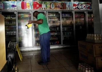 A man uses a flashlight to help others shop in the dark at a convenience store after the effects of Hurricane Ida knocked out power across New Orleans.