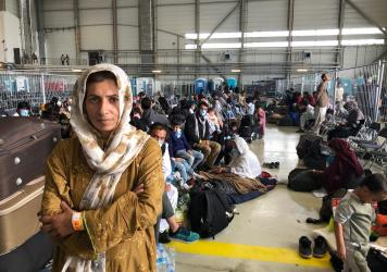 Afghan evacuees wait for the next flight to the U.S. in a fenced-in enclosure in a hangar at Ramstein Air Base in Germany. More than 25,000 Afghans have traveled through Ramstein to get to the United States.