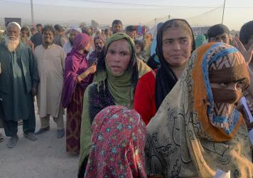 Afghan families gather after leaving their homeland and reaching the Pakistan side of the border, near the town of Chaman on Tuesday. Pakistan and other countries bordering Afghanistan have mostly closed their borders to Afghan refugees, with some except