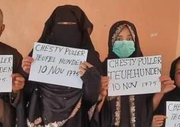 """Two family members show the signs they held so U.S. troops could spot them in the crowd at the Kabul airport. """"Chesty Puller"""" refers to a legendary U.S. Marine general. """"Teufel Hunden"""" means """"Devil Dog,"""" in German and is the name German troops used for M"""