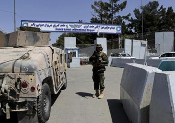 A Taliban soldier stands guard at the gate of Hamid Karzai International Airport in Kabul, Afghanistan, on Sunday.