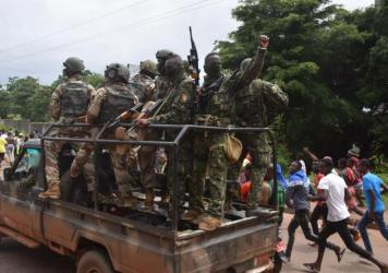 People celebrate in the streets with members of Guinea's armed forces after the arrest of Guinea's president, Alpha Conde, in a coup d'etat in Conakry on Sunday.