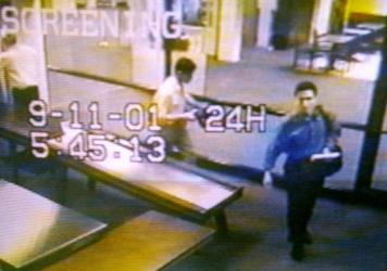 Two men identified by authorities as hijackers Mohamed Atta (right) and Abdulaziz Alomari (center) pass through airport security on Sept. 11, 2001, at Portland International Jetport in Maine in an image from airport surveillance tape released on Sept. 19