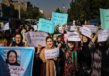 Protesters march in Kabul on Wednesday, a day after the Taliban announced their all-male interim government. At left, a protester carries a sign with a photo showing Banu Negar, a pregnant police officer who was killed in front of her relatives early thi