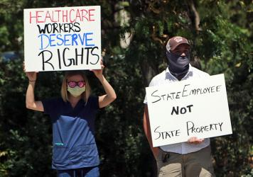 Nurse Katrina Philpot (left) protests against COVID-19 vaccine and mask mandates in Santa Fe, N.M., in August.