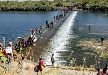 Migrants walk across the Rio Grande River carrying food and other supplies back to a makeshift encampment under the International Bridge in Del Rio, Texas, on Friday.