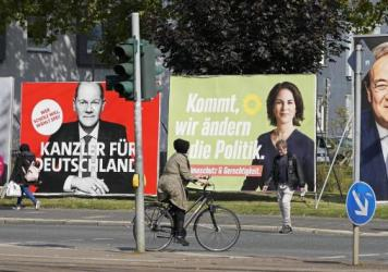 On Thursday, people in Gelsenkirchen, Germany, pass election posters of chancellor candidates Armin Laschet (from right) of the Christian Democratic Union, Annalena Baerbock of the Greens, Olaf Scholz of the Social Democratic Party and Christian Lindner