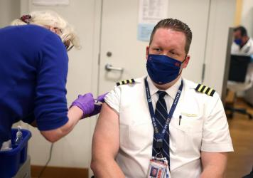 United Airlines pilot Steve Lindland receives a COVID-19 vaccine at O'Hare International Airport.